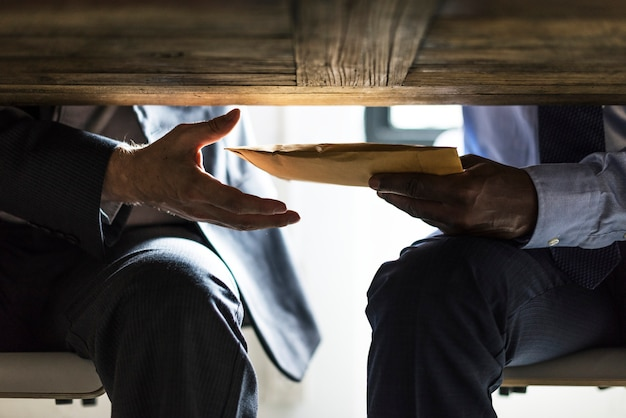 テーブルの下に文書を送信するビジネス人々