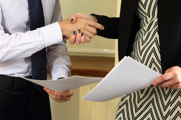 Business people shake hands after signing treaty papers