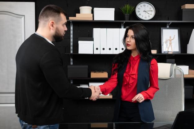ビジネスの人々は、スタイリッシュなオフィスでの会議で握手します。