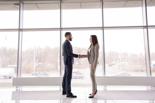 Business people shaking hands against window