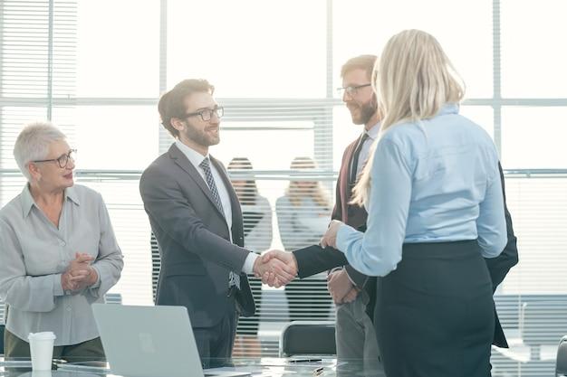 ビジネスコンセプトのオフィス会議で握手するビジネスマン
