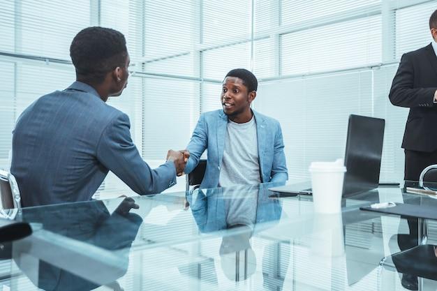 オフィス会議で握手するビジネスマン