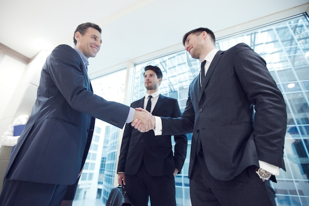 Деловые люди пожимают друг другу руки, заканчивая встречу в офисе
