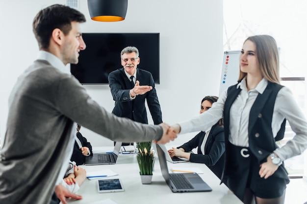 비즈니스 사람들이 악수하고 회의를 마무리합니다. 사무실에 새 관리자입니다.