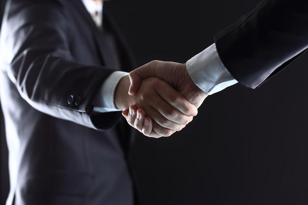 Деловые люди пожимают друг другу руки, заканчивая встречу