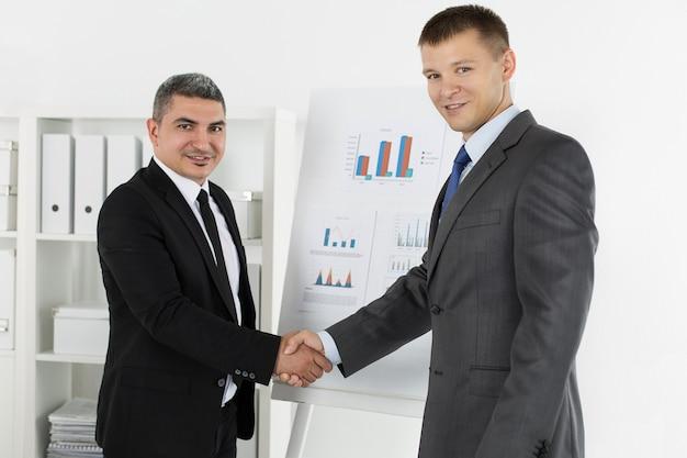 握手、会議を仕上げるビジネスマン