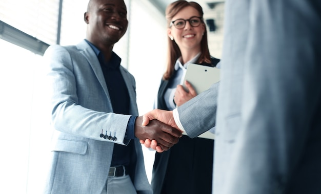 비즈니스 사람들이 악수하고 회의를 마무리합니다.