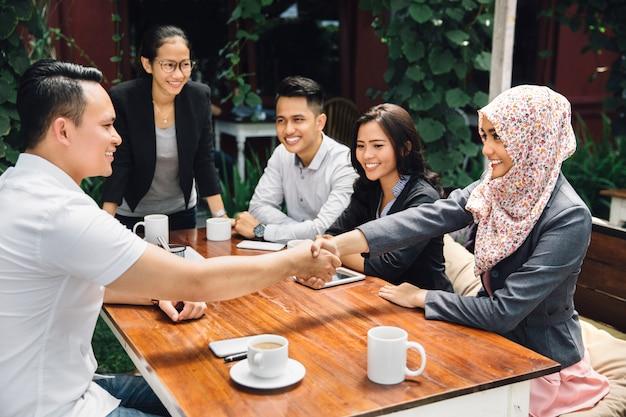 ビジネスの人々が握手、会議を仕上げる