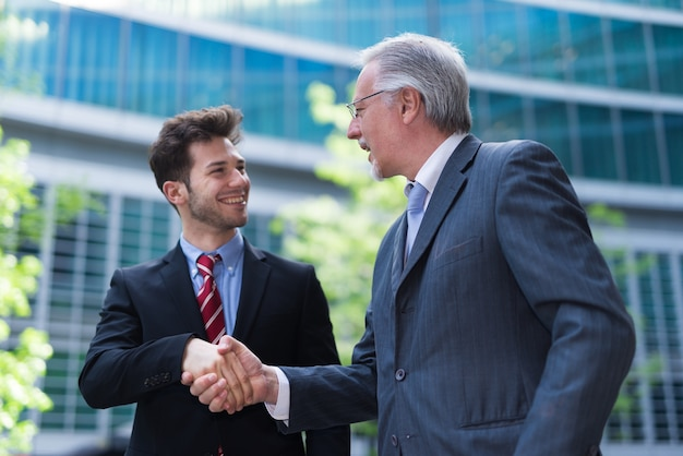 Business people shaking hands in front of an office