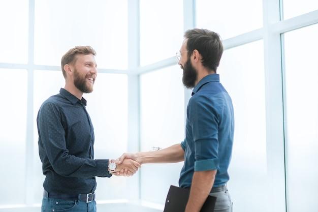Деловые люди, пожимая руки в ярком офисе концепции сотрудничества