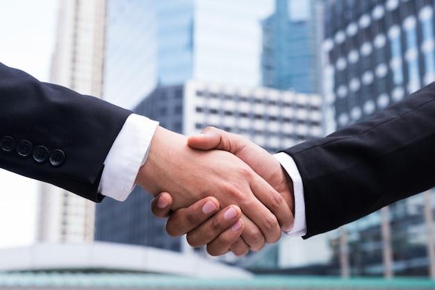 街で握手するビジネス人々