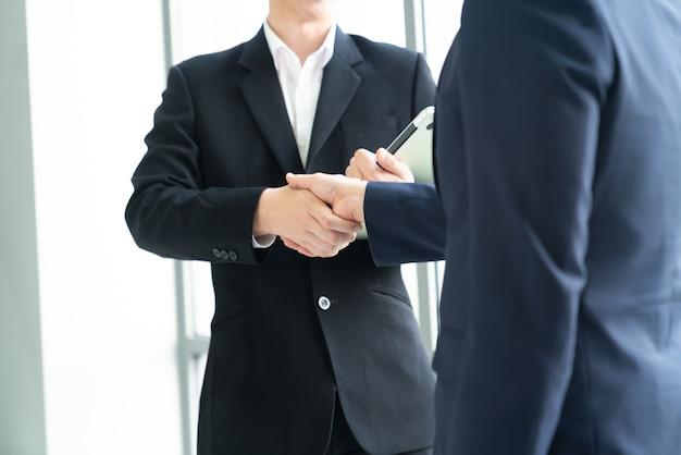 成功した会議、コンセプトチームワークの調整を終えてオフィスで握手するビジネスマン