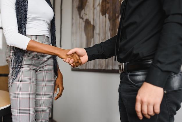 オフィスで握手するビジネス人々