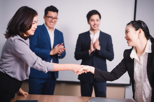 Business people shaking hands, between meeting in seminar room