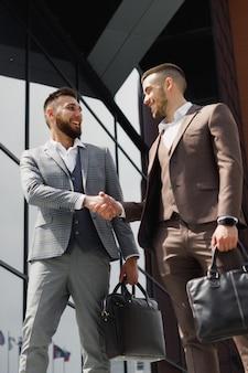 現代のオフィスビルの外で握手するビジネスマン
