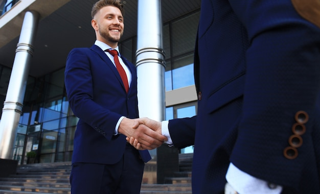 Business people shaking hands outside modern office building.