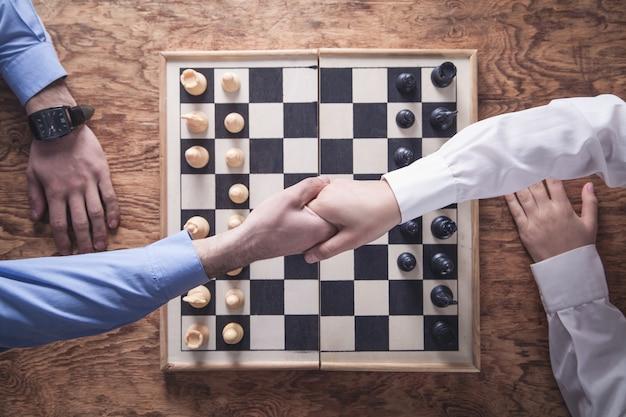 握手するビジネスマン。チェスゲームをする