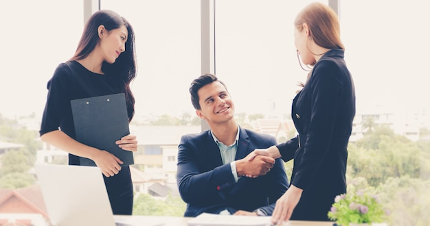 Business people shaking hands and smiling their agreement to sign contract and finishing u