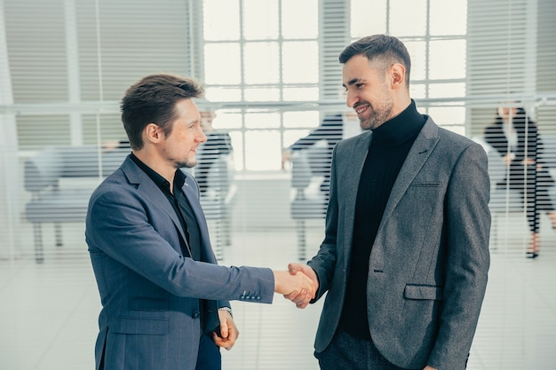 Business people shaking hands standing in the office lobby. business concept.