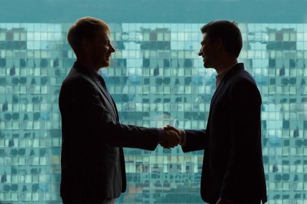 オフィスビルの緑の背景と握手するビジネスマン