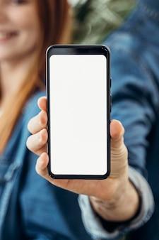 Gente di affari che mostra un telefono con schermo vuoto