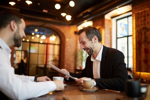 Деловые люди подписывают контракт в ресторане
