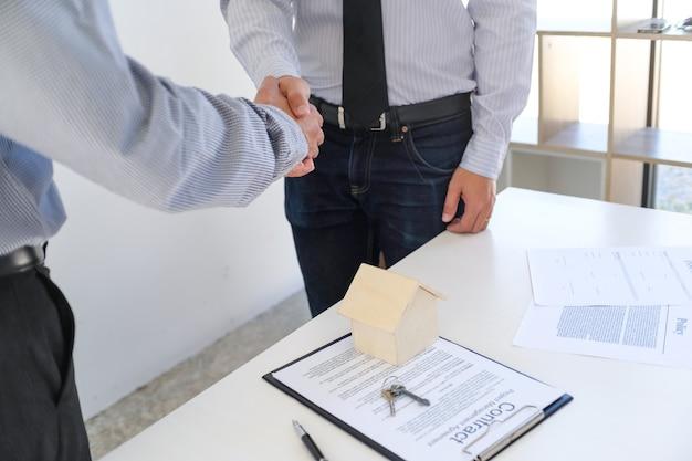 부동산 중개인과 계약을 체결하는 사업가들