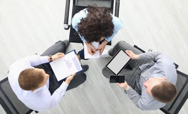 Деловые люди сидят на стульях с планшетами и коммерческими бизнес-диаграммами и обсуждают планы работы, вид сверху
