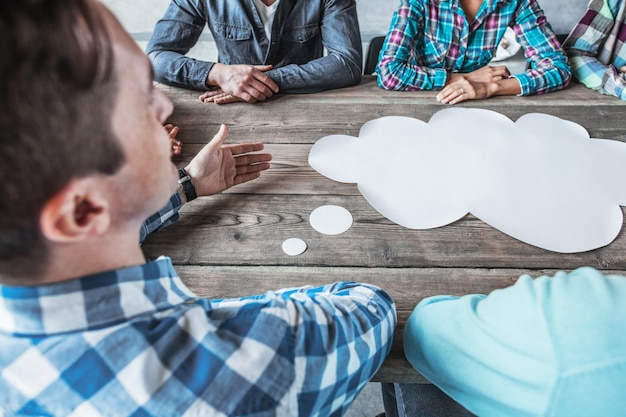 Business people sitting around the table with talking speech bubbles
