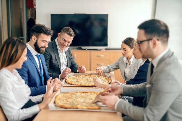 회의실에 앉아서 점심 피자를 먹는 사업 사람들.