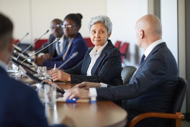 Деловые люди сидят за столом и разговаривают друг с другом во время бизнес-конференции