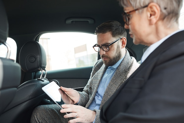 Business people sitting on back seat and using digital tablet for their work during car ride