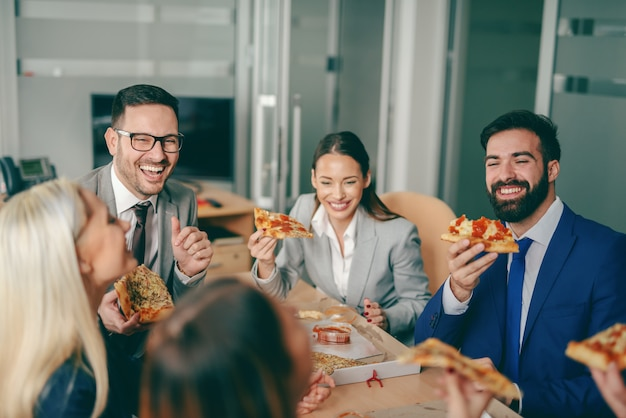 Business people sitting at boardroom and having pizza for lunch.