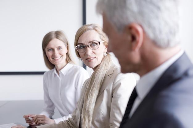 並んで座って仕事をしているビジネスマンは、眼鏡をかけた成熟した女性に焦点を当てる