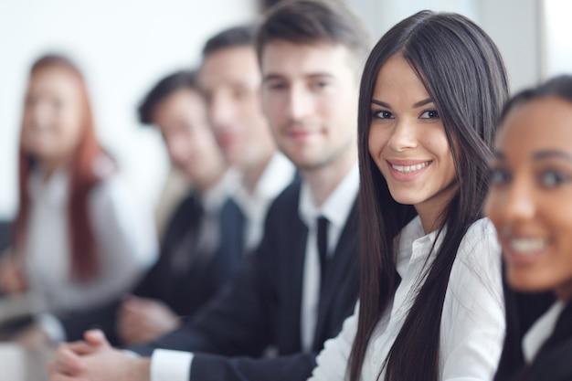 Деловые люди, сидящие в ряду и работающие, сосредотачиваются на красивой женщине