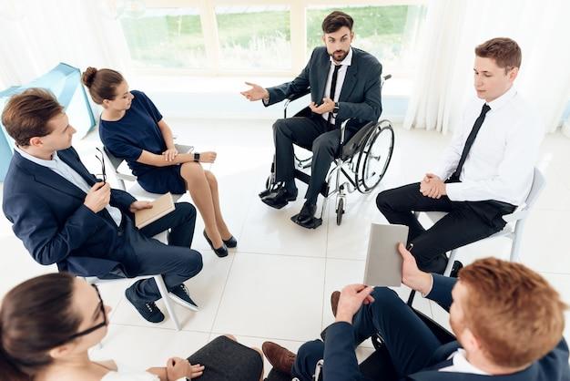 Деловые люди сидят в инвалидных колясках и обсуждают.
