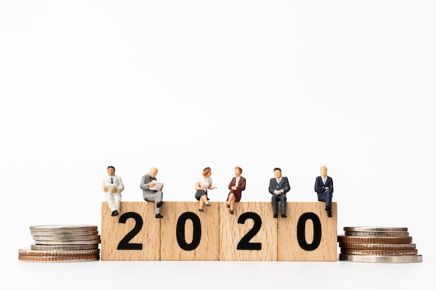 Business people sitting on wooden block number 2020
