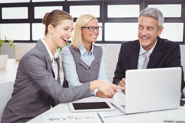 Business people smiling while discussing over laptop