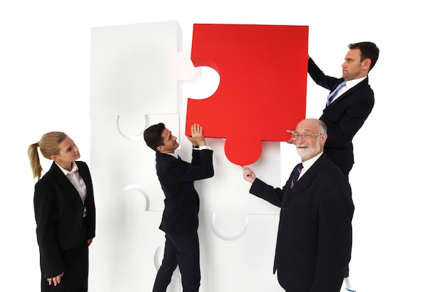 Business people solving problems assembling puzzle isolated on white background