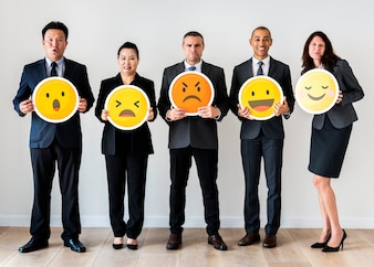 Business people standing and holding emoji icons