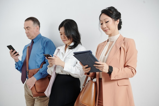 다양한 가제트에서 온라인으로 전자 메일이나 기사를 읽고 서 있는 사업가들