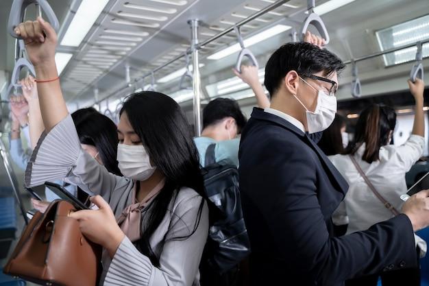 지하철 대중 교통 지하철에 서있는 사업 사람들. 태블릿과 스마트 폰을 사용하는 사람. 얼굴 마스크를 착용하는 사람들. 공공 여행에서 코로나 바이러스 독감 바이러스.