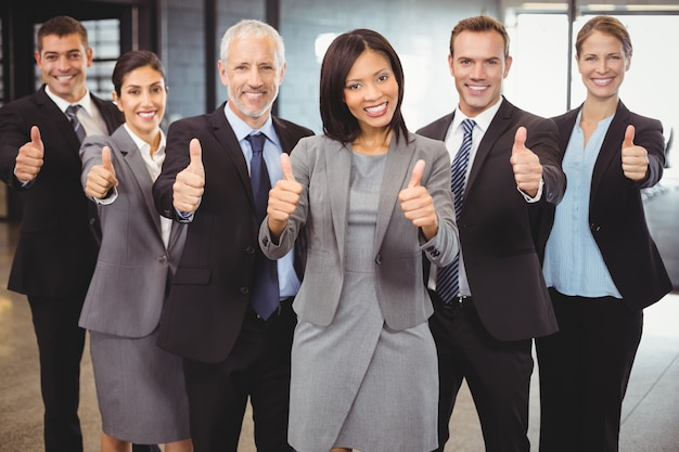 Business people standing together and giving thumbs up