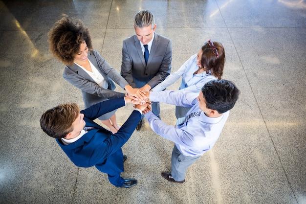 彼らの手で立っているビジネス人々のオフィスに積み上げ