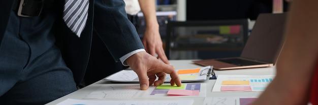 オフィスで成功したチームワークの概念のテーブルでチャートやドキュメントを勉強しているビジネスマン