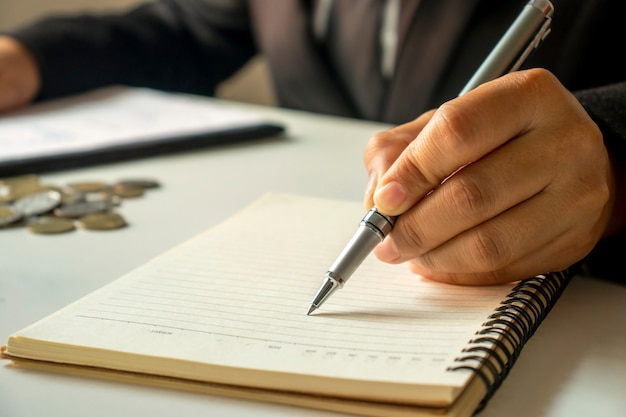 Деловые люди делают записи о доходах и расходах в блокноте.