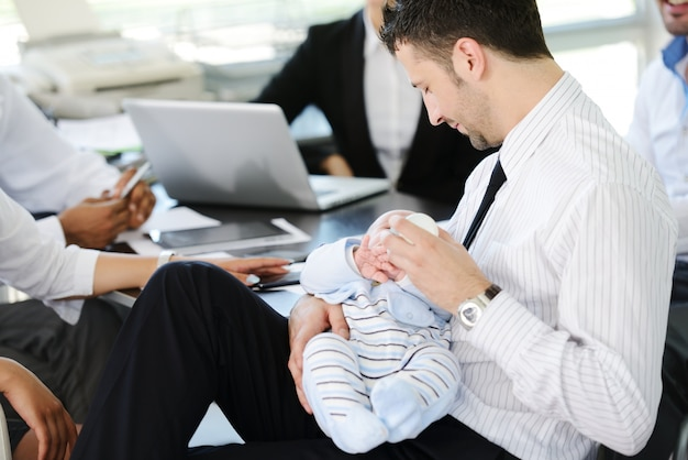 Business people taking care of baby in office