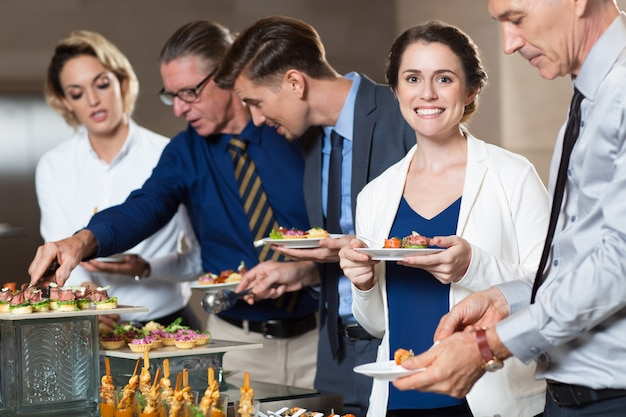 Business people taking snacks from buffet table
