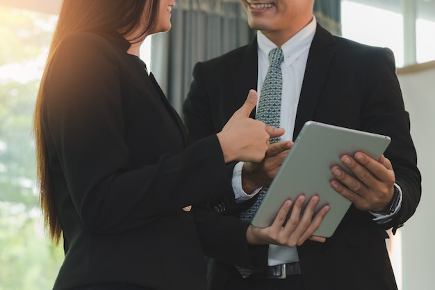 Деловые люди говорят и улыбается содержание на планшете вместе, концепция бизнеса