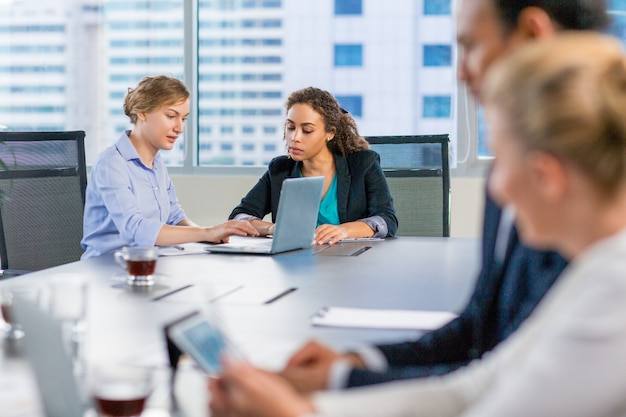 会議テーブルで話しビジネス人々
